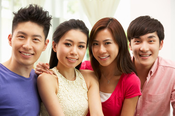 Group Of Young Chinese Friends Relaxing On Sofa At Home
