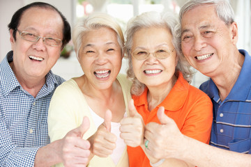 Group Of Senior Chinese Friends Relaxing On Sofa At Home