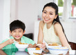 Chinese Mother And Son Sitting At Home Eating A Meal