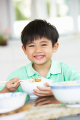 Young Chinese Boy Sitting At Home Eating Meal