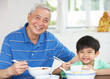Portrait Of Chinese Granddad And Grandson Eating Meal Together