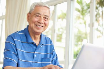 Senior Chinese Man Sitting At Desk Using Laptop At Home