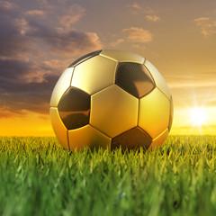 Fussball gold schwarz 3D auf Rasen im Sonnenuntergang