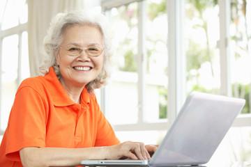 Senior Chinese Woman Sitting At Desk Using Laptop At Home