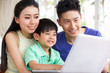 Chinese Family Sitting At Desk Using Laptop At Home