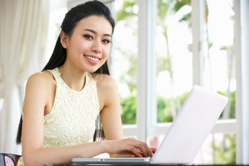 Young Chinese Woman Sitting At Desk Using Laptop At Home