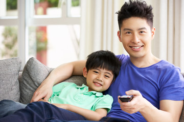 Chinese Father And Son Sitting And Watching TV On Sofa Together