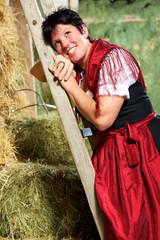 Hübsche junge Frau im Dirndl auf Holzleiter