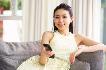 Young Chinese Woman Sitting And Watching TV On Sofa At Home