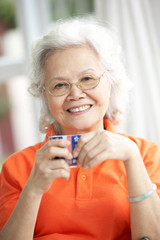 Senior Chinese Woman Drinking Tea On Sofa At Home