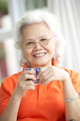 Senior Chinese Woman Drinking Tea On Sofa At Home