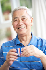 Senior Chinese Man Drinking Tea On Sofa At Home