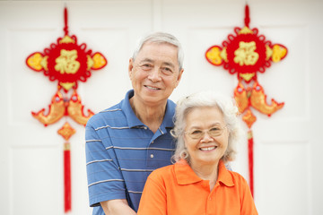 Senior Chinese Couple Outside Home Decorated With Feng Shui