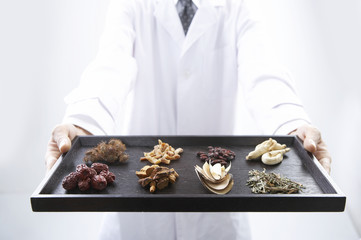 doctor holding medicinal herbs on a tray