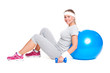 sportswoman sitting with ball and dumbbells