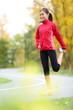 Runner woman stretching thigh