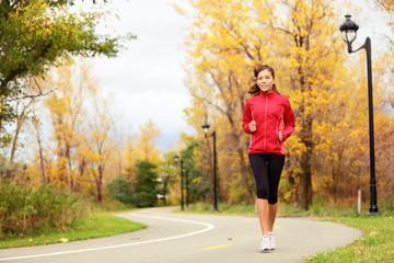Fall running - woman jogging in autumn
