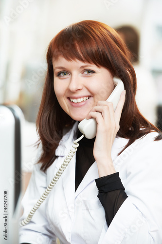 Pharmacy chemist woman in drugstore with phone