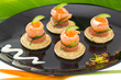 "Red salmon roll with cheese, caviar and cucumber on"" blinis"""