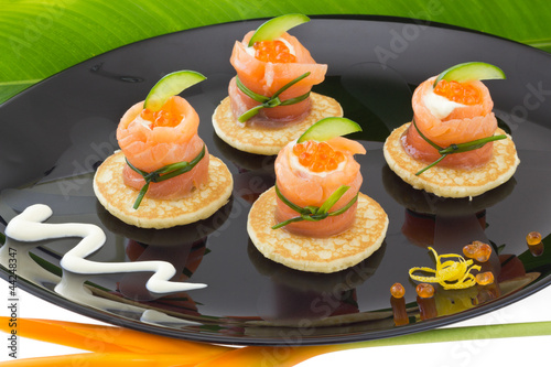 """Red salmon roll with cheese, caviar and cucumber on"""" blinis"""""""