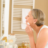 Senior woman clean face with cotton pad