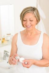 Senior woman bathroom hold cotton pad cream