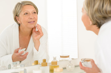 Senior woman look at herself bathroom mirror reflection