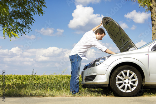 Man fixing a broken car by the road