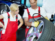 Mechanic in a garage checking tyre pressure with trainee