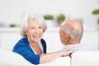 attraktive seniorin mit ihrem mann auf dem sofa