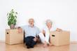 senioren-paar sitzt lächelnd zwischen umzugskartons