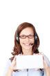 lächelnde frau mit headset zeigt weißes schild