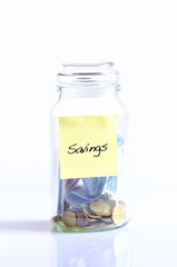 Glass jar with coins for savings.