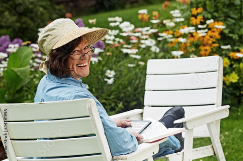 woman with book and e-book in the garden