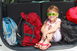 a little girl  sitting in the car with backpacks