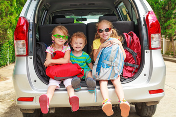 two little girls  and boy sitting in the car with backpacks
