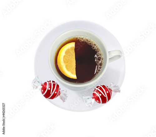 cup of tea with lemon slice and candies isolated on white
