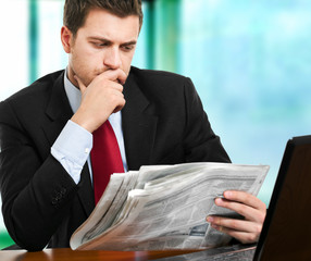 Businessman reading a newspaper at his desk
