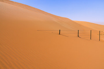 Fence drowned by huge sand dune in the United Arab Emirates