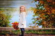 autumn happy little girl has fun playing with fallen golden leav