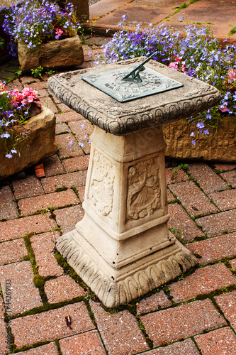 ornamental sundial in a small paved garden