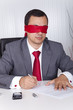 Blindfold businessman working