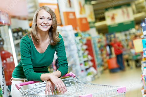 One shopping woman with cart at supermarket