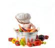 Bambino con cappello da cuoco dentro la pentola con ortaggi