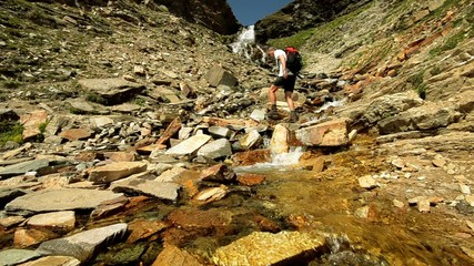 hiker crossing stream
