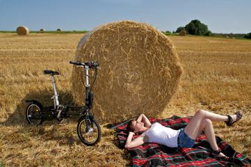junge Frau auf Wiese mit Fahrrad beim Entspannen