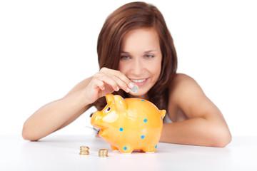 lächelnde frau wirft geld in ihr sparschwein