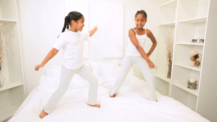 Young Ethnic Sisters Dancing Bed