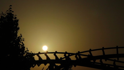 Line of dragon roller coaster rail (silhouette at sunset)