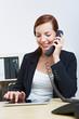 Frau im Büro telefoniert neben Tablet Computer